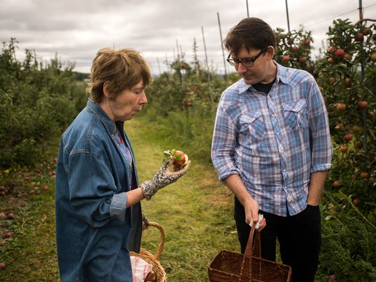 Vestal resident Cheryl Kerr takes a bite from a freshly picked apple while her son Larry Kerr, visiting from New York City, looks on while picking apples Thursday at Apple Hills in Binghamton.