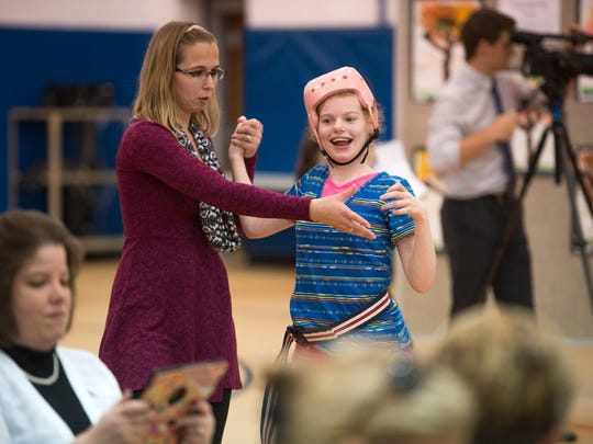 MOVE teacher Crystal Boll, left, escorts student Summer Schenk, 20, into the Broome Tioga BOCES gymnasium during a Mobility Parade on Friday.