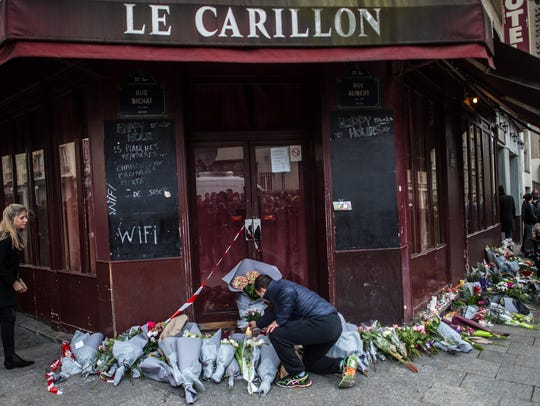 A man leaves flowers at the main entrance of Le Carillon