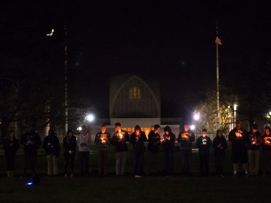 University of Rochester students light candles in the school's Eastman Quad.