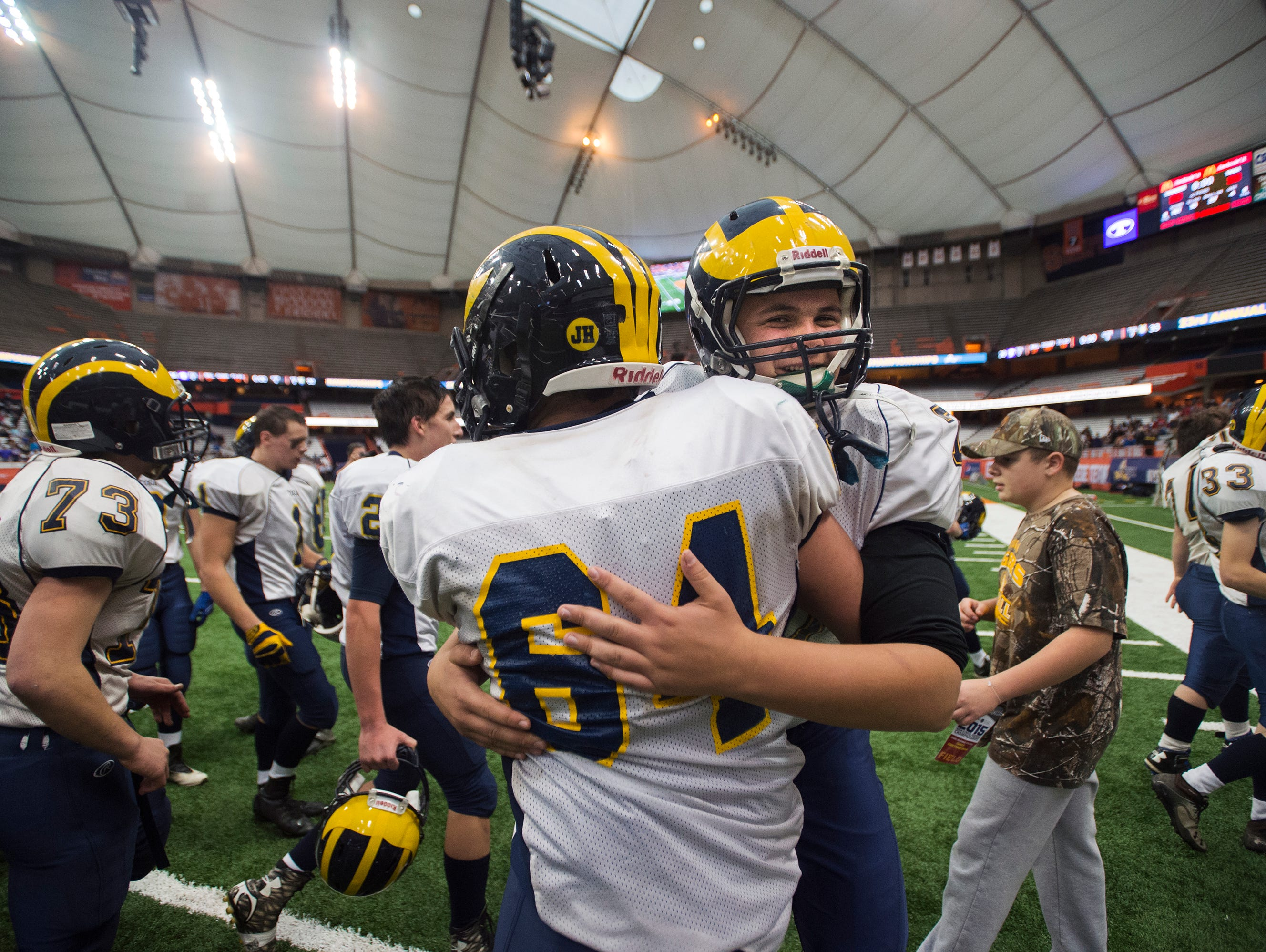Tioga players Peter Kuhlman, right, and Caleb Manwaring hug after beating Ticonderoga 33-26 to win the 2015 Class D State Championship in Syracuse on Friday, Nov. 27, 2015.