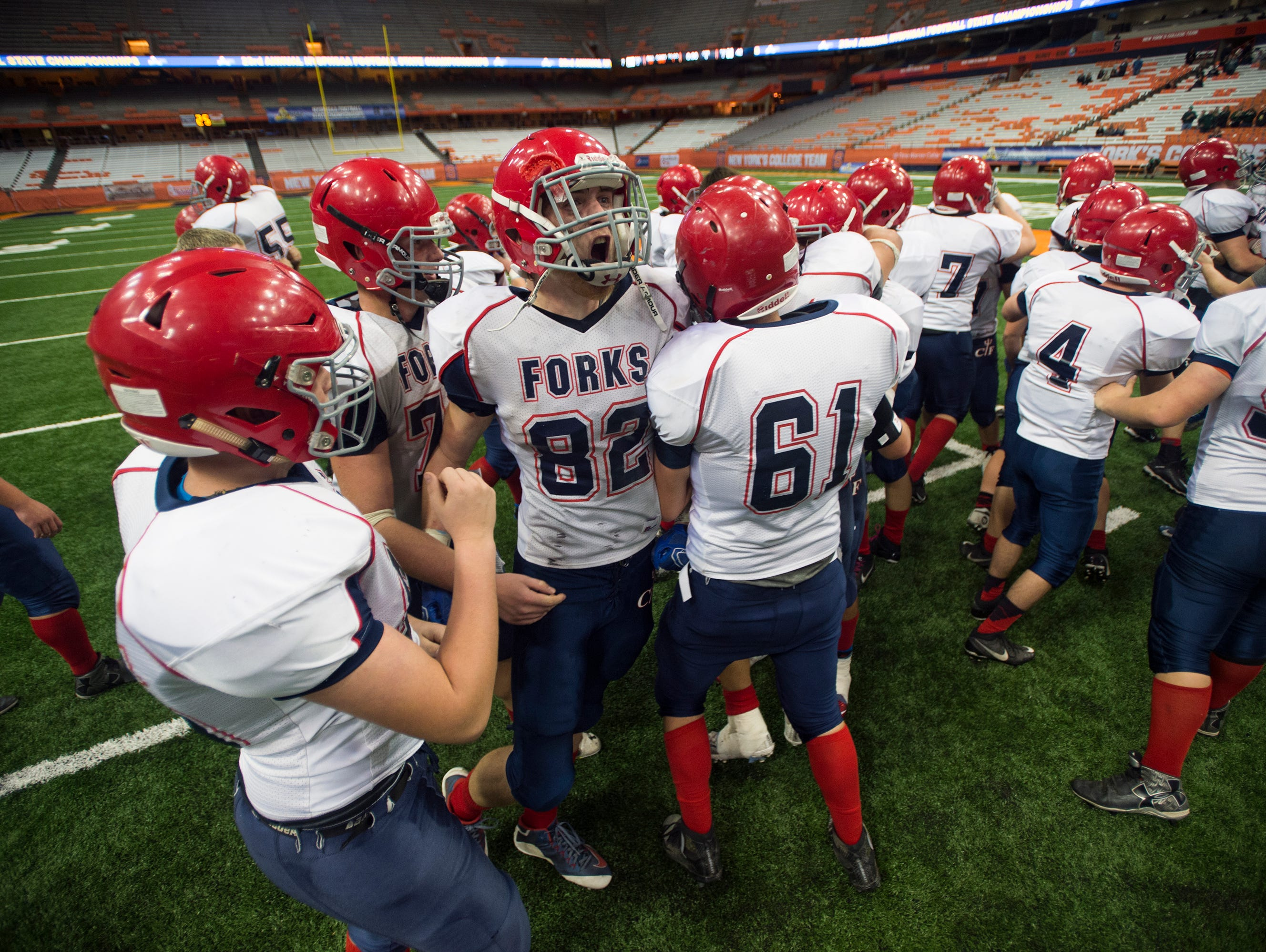 Chenango Forks players celebrate on the field following their 42-7 win over Greenwich to win their third straight Class C state championship in Syracuse on Friday, Nov. 27, 2015.