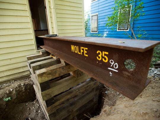 A large beam used to lift the foundation of the home sticks out of a first-floor window.