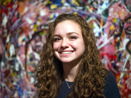 """Marla Olmstead, 15, sits in front of her painting """"Faces"""" in her Binghamton home on Friday, Dec. 18, 2015."""
