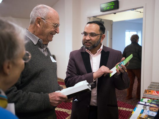 Ali Azam, of Binghamton, a regular attendee of the mosque talks to Barbara and Richard Bartholomew, of Kirkwood, during Saturday's open house event at the Islamic Organization of the Southern Tier in Johnson City.