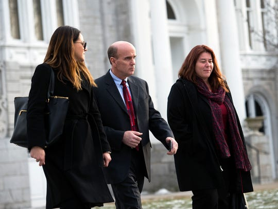 Cal Harris, center, leaves Schoharie County Court with