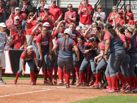 Cajun Softball players greet Lexie Elkins at home plate