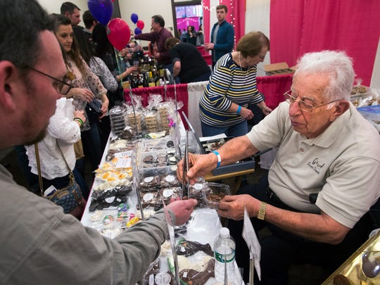 Anthony Astarita, right, serves a sample of his chocolate to a customer from behind his G & A Sweet Treats booth at the first-ever Binghamton Wine and Chocolate Festival on Saturday.