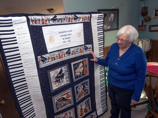 Dori Schriber stands next to a quilt that was made by club member Robin DeSantis to honor the 90th anniversary of the Binghamton Harmony Club inside her Endicott home on Wednesday, March 16, 2016.