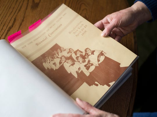 Dori Schriber looks through a binder of research she compiled on the history of the Binghamton Harmony Club inside her Endicott home on Wednesday, March 16, 2016.