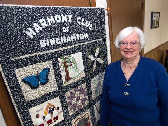 Dori Schriber stands next to a quilt that was made by a group of members to honor the 75th anniversary of the Binghamton Harmony Club inside her Endicott home on Wednesday, March 16, 2016.