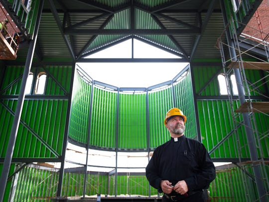 Father Dwight Longenecker looks around at the construction