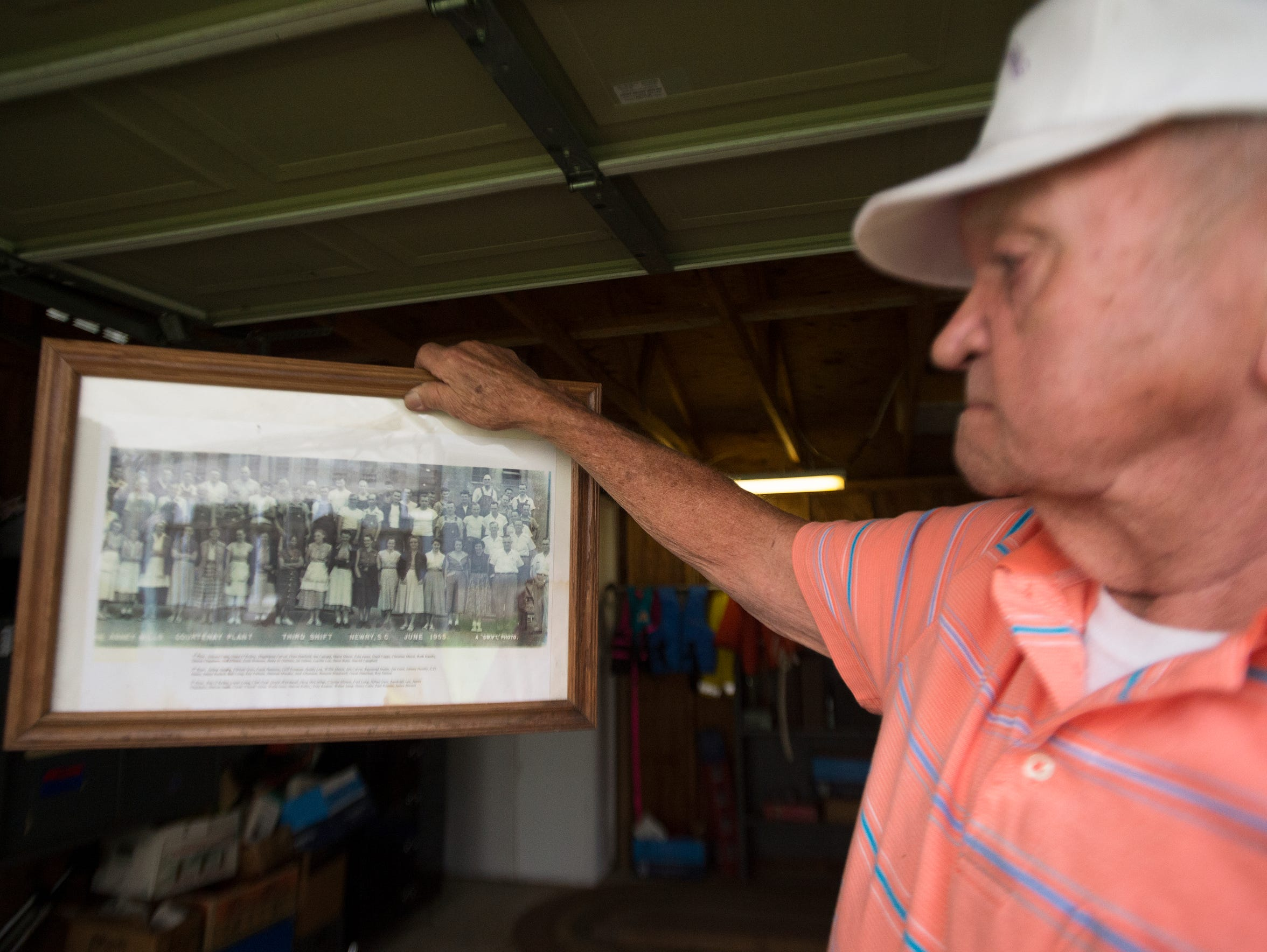 John Taylor, 83, looks at a photograph from the time