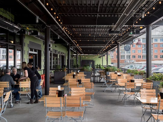 The patio dining area of Cochon Butcher, I Love Juice