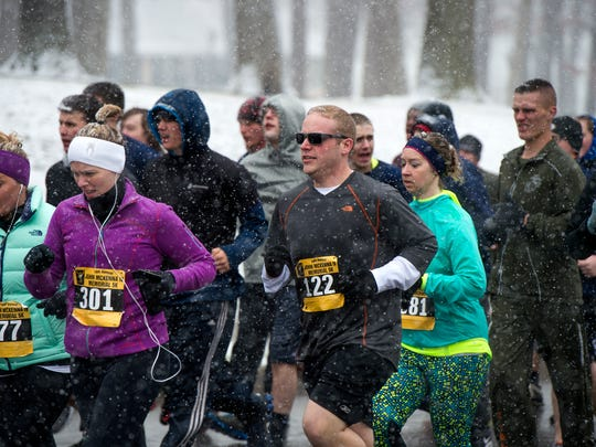 People run amid a steady snowfall during the 10th Annual John J. McKenna IV Memorial 5K at Recreation Park on Saturday morning.