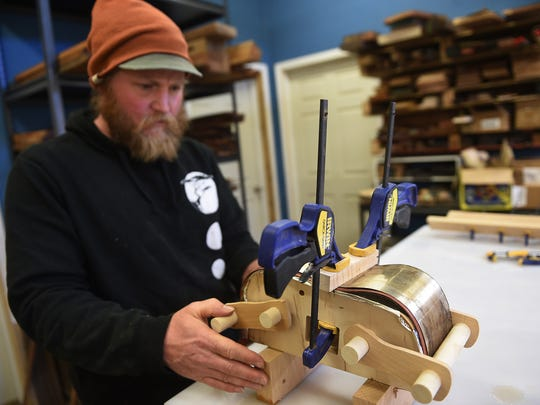 Luthier Devin Price works a custom press while building a ukulele at TyDe Music studio in Kings Beach on April 4, 2016.