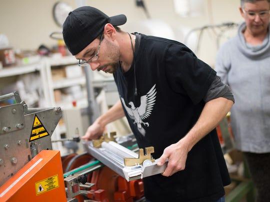 Robert Austin operates the mesh mounting machine at Susan Jablon Mosaics.
