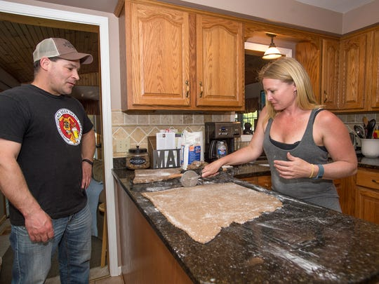 Ed Kincer looks on as his girlfriend Casey Parker cuts dough while preparing a batch of Hungry Hounds Beer Grain Dog Treats inside her Conklin home on Thursday, May 12.