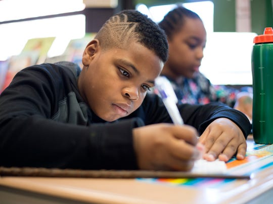 Ethan Abrams, 10, writes about visiting Universal Studios during a writing workshop at Woodrow Wilson Elementary School in Binghamton.