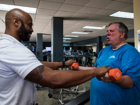 YMCA Wellness Director Fred Shelby gives resistance as Ken Mullinax does a bicep curl exercise on Tuesday, May 31, 2016 at the downtown YMCA in Montgomery, Ala. Mullinax, who currently weighs 340 pounds, is trying to lose 100 pounds.