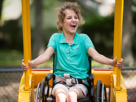 Kasey Shoop, 12, rides a Liberty Swing at OurSpace Park during the park's opening ceremony Tuesday. The swing is designed for children in wheelchairs.