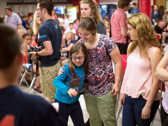 Chenango Bridge third-grader Brynn Vinsevich, 9, hugs Chenango Valley High School senior Trisha Illsley, 18, after receiving the sculpture figurine of her drawing of a monster.