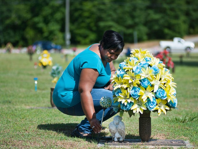 Michelle McCarroll cleans off her brother's grave in