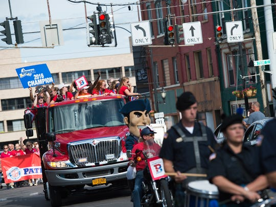 Binghamton High School athletes from the track and softball team's ride down Court Street during a parade celebrating their recent state championships on Tuesday evening.