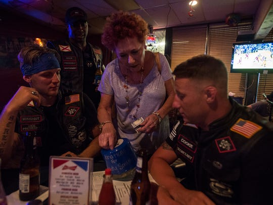 A woman donates 200 dollars during a fundraiser for Aaron Cody Smith on Saturday, Jun. 25, 2016 at Pratt Pub & Oyster Bar in Prattville, Ala. Regulator members from left to right: Wingnut, Bear and Cookie.