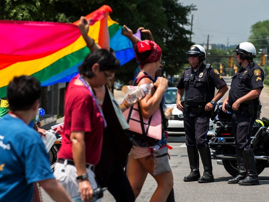 Law enforcement officers standby as people walk to the Capitol during the Montgomery Pride march on Sunday, Jun. 26, 2016 in Montgomery, Ala.