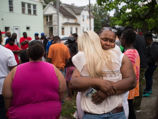 Elena Turrell-Nash receives a hug during a candlelight vigil in memory of her husband William Nash Jr.