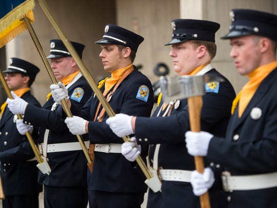 Binghamton firefighters stand at attention during a memorial for firefighters who have died over the past year.