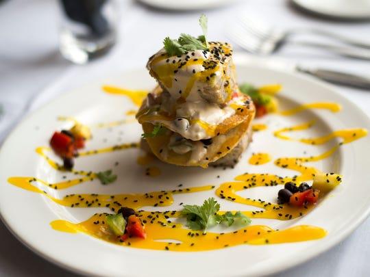 A marinated tuna stack made with black bean mango salsa, won-tons, and ginger cream.