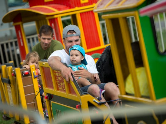 Mike Seman, of Binghamton, holds 1-year-old Mia Iacovelli on a train ride during Spiedie Fest on Friday.