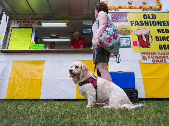 Buddy, a 2-year-old service dog, waits while his owner Angela Hodson, of Woodbury Hills, New Jersey, orders refreshments at Spiedie Fest on Saturday.