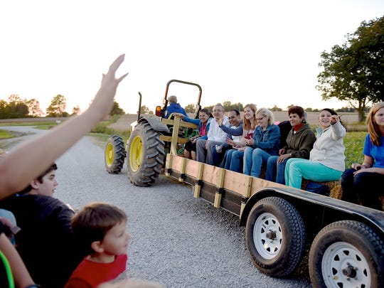 Friends greet one another as their hay ride wagons pass each other at Cates Farm Corn Maze and Pumpkin Patch in October of 2014.