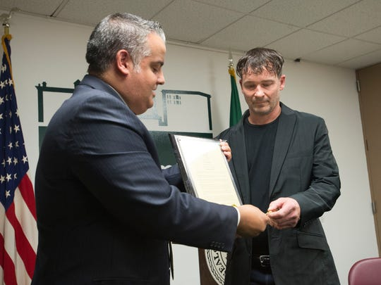 Binghamton Mayor Richard David presents a key to the City of Binghamton to Doug Kumpon, who helped a woman escape a burning car during a crash on Aug. 25.