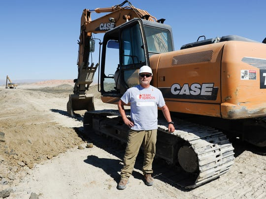 Volunteer Jim Simmons poses next to an excavator at Red Hill Bay near the shore of the Salton Sea. Simmons has been helping build a berm for a wetlands project that will provide habitat for birds.