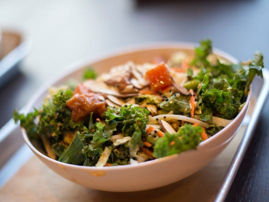 CoreLife's tuna poke grain bowl with kale, shredded cabbage, cumber, quinoa, carrots, scallions, ginger edamame, avocado, sesame seeds, and almonds.