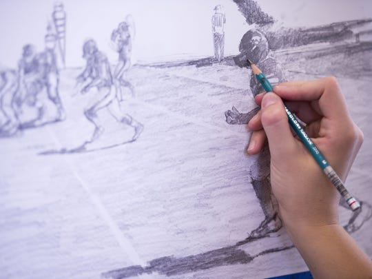 Elinor Krieger-Coble works on her football drawings in her studio in the Visual Arts Building. Elinor has been attending Iowa football games this season with a field pass to collect material to use to create an artist's interpretation of the gameday experience at Kinnick Stadium