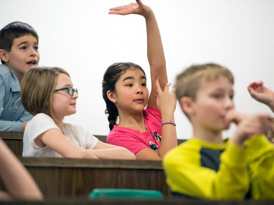 Glenwood Elementary fourth-grader Arden Kaldis, 9, eagerly raises her hand to answer a question during Wednesday's chemistry magic show at Vestal High School.