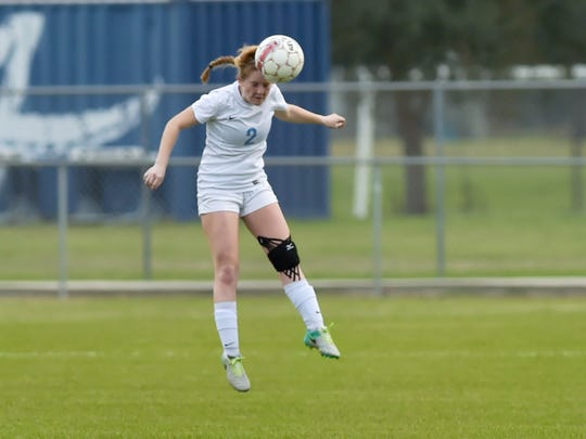 Beverly Richard makes a head pass as Ascension Episcopal