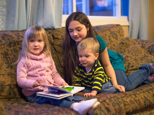 Left, Mattie, 3, Titus, 2, and Tiana, 11, far right, read a book inside the Berkshire home Chandler family is renting.