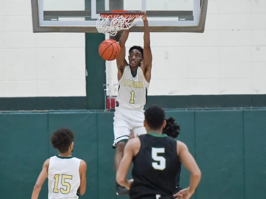 Myles Hutchenson dunks the ball as Acadiana takes on