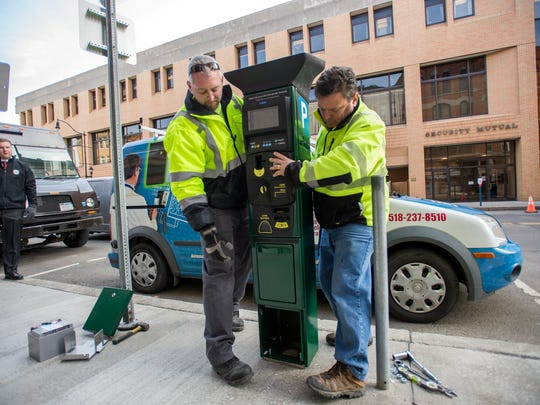 Todd Schroeder, right andSteve Crothers, left, of Access technology Integration Inc. install a parking meter along Court Street on Thursday, March 9, 2017.