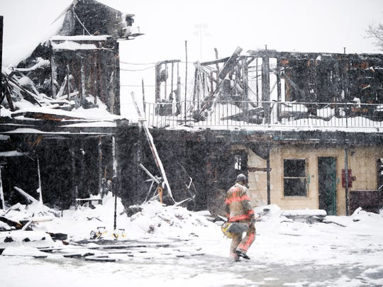 A firefighter walks in front of the scene of an overnight fire at the Skylark Motel in Vestal on Tuesday, March 14, 2017. One person was confirmed dead and another was taken to the hospital with non-life threatening injuries.
