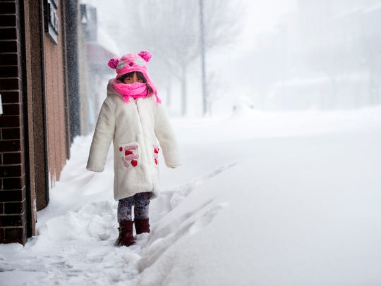 Erin Wu, 5, plays in the snow outside China Doll on