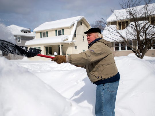 Larry Koch shovels the sidewalk in front of his home