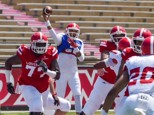 Offensive lineman Adrian Goodacre (77), shown here blocking for quarterback Jordan Davis during UL's spring game earlier this month, is among a group of Cajuns planning a mission trip to Haiti.