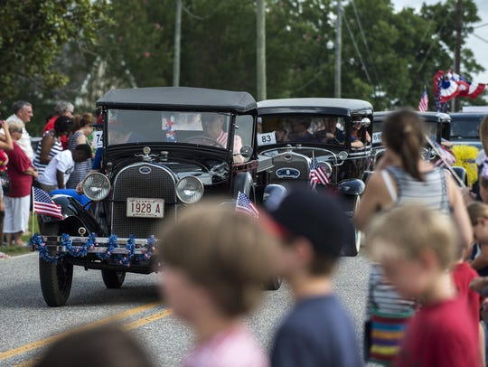 Parade participants in vintage cars drive down the